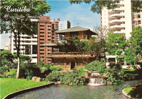 A Japanese house on the side of a river, in between some tower blocks.