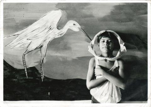 "A child with a jaw bone around his head standing in front of a painting of a white stork. Photo: ""Tehuantepec"", G. Iturbide, 1985."